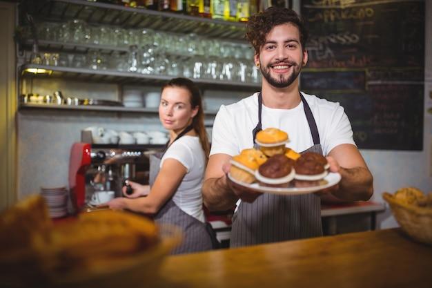 Ritratto di cameriere in possesso di un piatto di torta tazza al banco