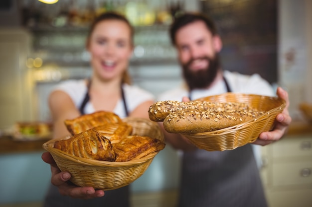 Portrait of waiter and waitress holding a basket of bread