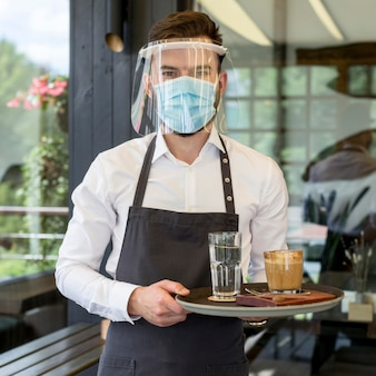 Portrait waiter with mask serving