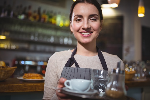 Portrait of waitress holding cup of coffee