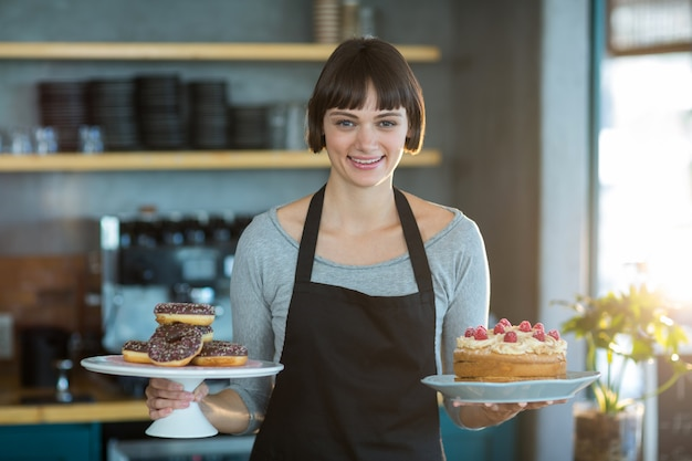 Portrait of waitress holding doughnuts and cake in cafe