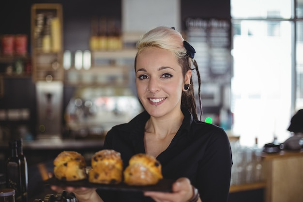 Portrait of waitress holding tray of muffins at counter