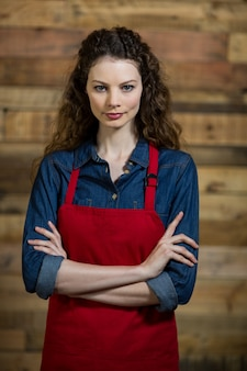 Portrait of waitress standing with arms crossed against wooden wall