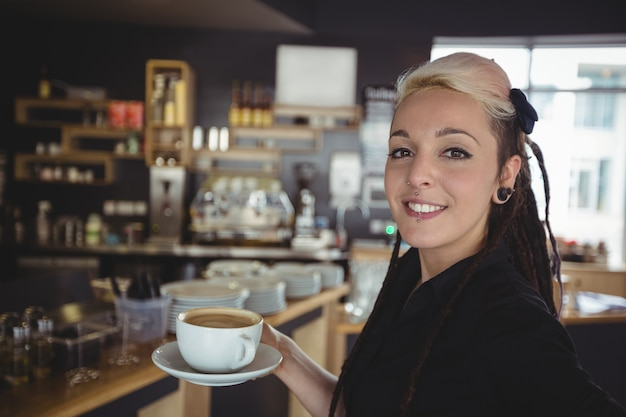 Portrait of waitress standing with cup of coffee