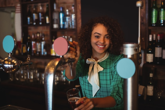 Portrait of waitress using beer tap at counter