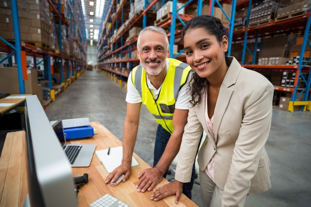 Portrait of warehouse manager and worker working together