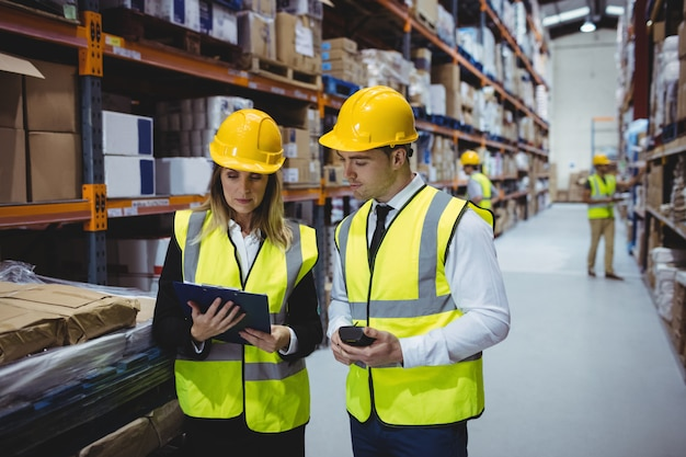 Portrait of warehouse managers looking at clipboard