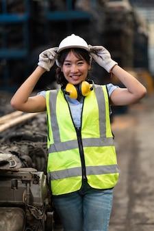 오래된 자동차 부품의 대형 유통 창고에서 일하는 초상화 창고 관리자 또는 작업자 아시아 여성.