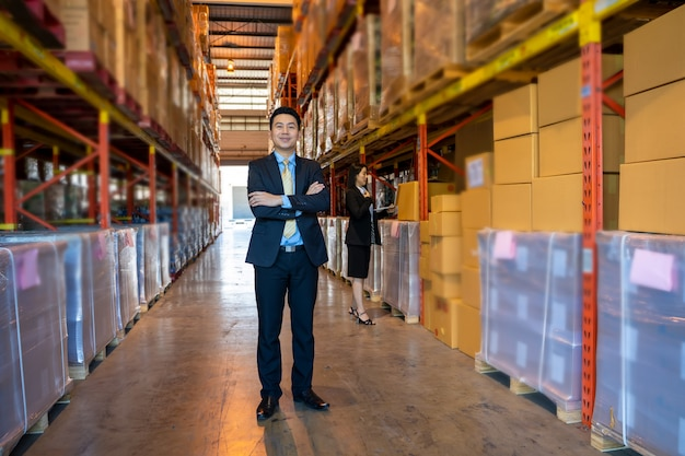 Portrait of warehouse worker with business people with crossed arms standing in a large warehouse.