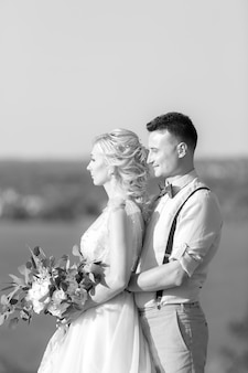 Portrait of wedding couple on the nature in summer day. the bride and groom hugging at the wedding. black and white photo