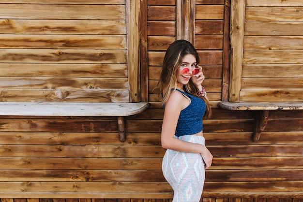 Ritratto di ragazza alla moda ben costruita in gonna midi e occhiali da sole colorati sorridente, in piedi con l'espressione del viso sorpreso
