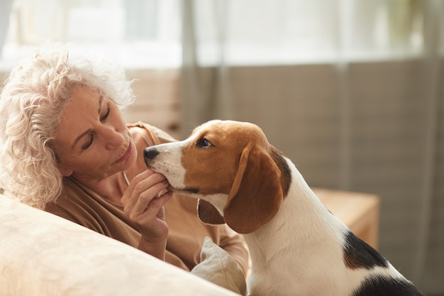 Portrait of white haired senior woman playing with dog and giving him treats while sitting on couch in cozy home interior