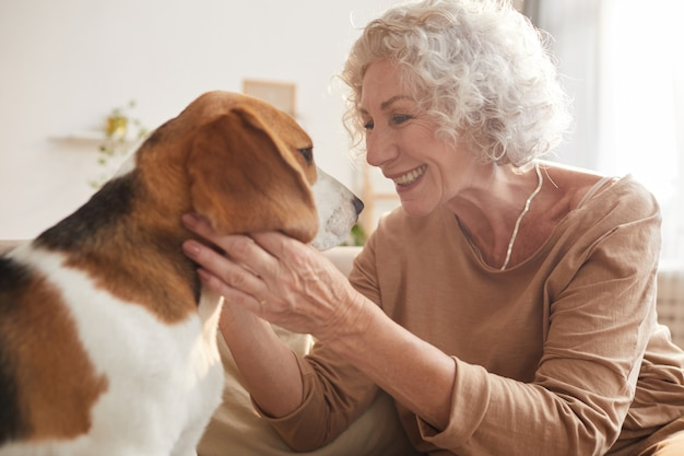 Portrait of white haired senior woman playing with dog and smiling while sitting on couch in cozy home interior