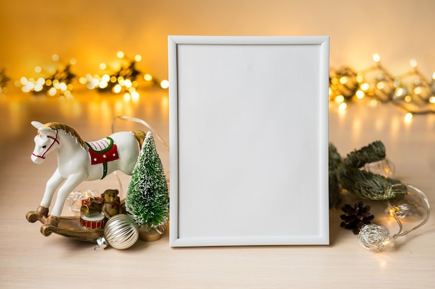 Портретный белый макет фоторамки на столе с огнями бокен и рождественскими украшениями. фото высокого качества