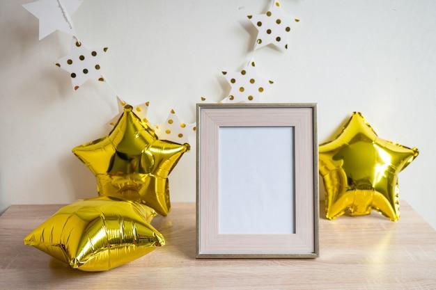 木製のテーブルの上の肖像画の白い額縁モックアップゴールドバルーン誕生日コンセプト白い壁の背景スカンジナビアのインテリア垂直