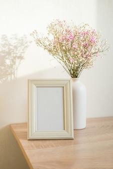 木製のテーブルの上の肖像画の白い額縁のモックアップ。カスミソウと現代のセラミック花瓶。白い壁の背景。スカンジナビアのインテリア。垂直。