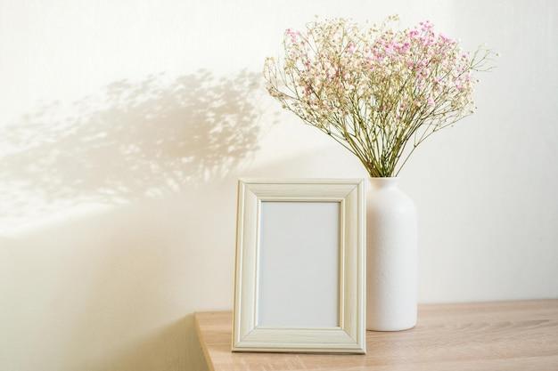 나무 테이블에 세로 흰색 액자 모형입니다. 안개꽃과 현대적인 세라믹 꽃병. 흰 벽 배경입니다. 스칸디나비아 인테리어. 세로.