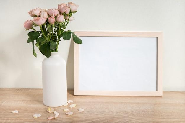 木製のテーブルの上の肖像画の白い額縁モックアップバラとモダンなセラミック花瓶白い壁の背景スカンジナビアのインテリア