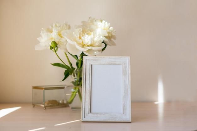 木製のテーブルの上の肖像画の白い額縁モックアップ牡丹とモダンなガラスの花瓶白い壁の背景スカンジナビアのインテリア垂直