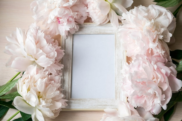 木製のテーブルに肖像画の白い額縁のモックアップ牡丹とモダンなガラスの花瓶