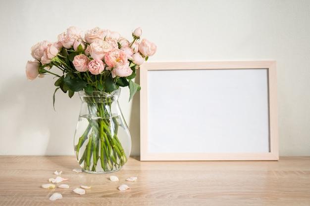 木製のテーブルの上の肖像画の白い額縁モックアップバラとモダンなガラスの花瓶白い壁の背景スカンジナビアのインテリア