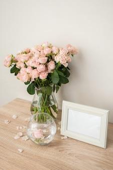 나무 테이블에 세로 흰색 액자 모형 장미와 현대 유리 꽃병 흰 벽 스칸디나비아 인테리어
