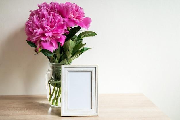 木製のテーブルの上の肖像画の白い額縁モックアップ牡丹とモダンな花瓶白い壁の背景スカンジナビアのインテリア