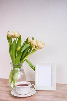 나무 테이블에 세로 흰색 액자 모형입니다. 튤립과 coffe 컵 현대 꽃병입니다.