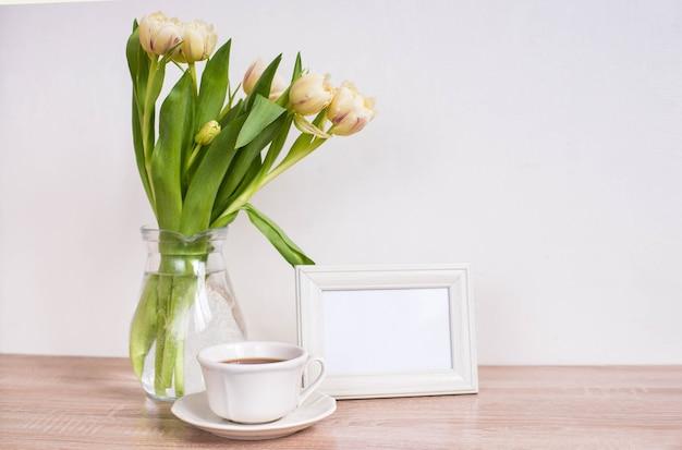 木製のテーブルの上の肖像画の白い額縁のモックアップ。チューリップとコーヒーのカップが付いている現代の花瓶。
