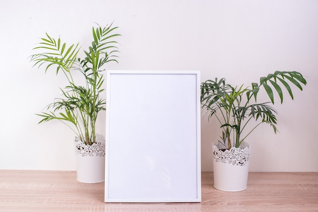 Portrait white picture frame mockup on wooden table. modern ceramic vase.  white wall background. scandinavian interior.