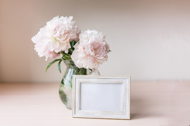 Portrait white picture frame mockup on wooden table modern glass vase with peony