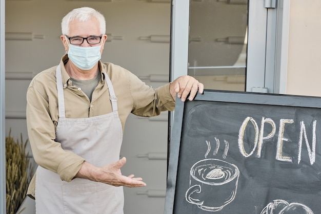 Portrait of whitehaired mature owner of store or cafe pointing at open signboard