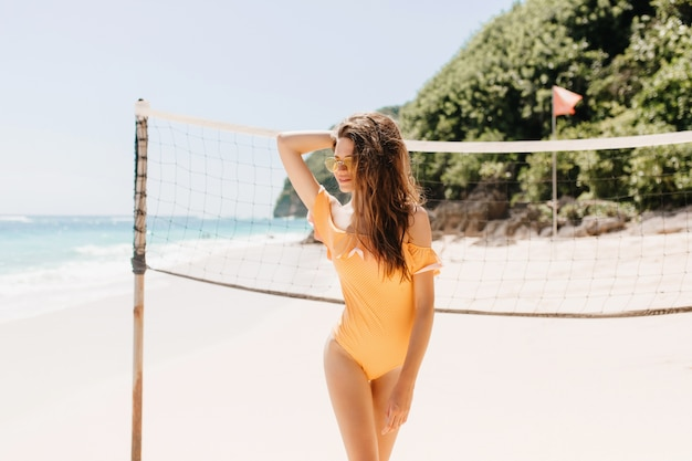 Ritratto di accattivante ragazza bruna in piedi vicino al set di pallavolo. foto all'aperto di splendida donna abbronzata in costume da bagno arancione in attesa di gioco in spiaggia.