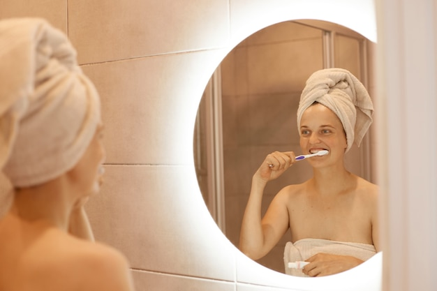 Portrait of winsome woman with bare shoulders brushing her teeth, having hygiene procedures after taking shower, standing in bathroom with white towel on her hair.