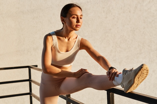 Portrait of winsome woman with ponytail wearing white top and beige leggins, stretching leg