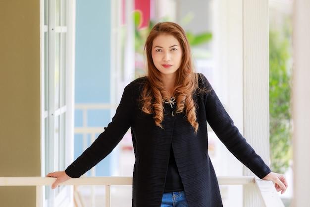 Портрет с размытым фоном из длинных волос, красивая азиатская женщина в черном свитере и синих джинсах с улыбающимся лицом в позе уверенности в себе