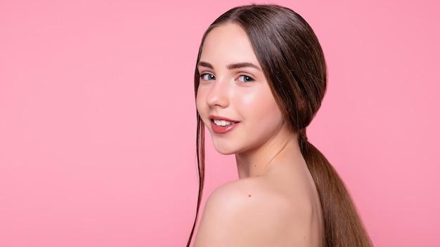 분홍색 배경에 격리된 현대적인 화장, 완벽하고 이상적인 피부를 가진 매력적이고, 명랑하고, 트렌디하고, 매력적이고, 사랑스럽고, 벌거벗고, 셔츠를 입지 않은 소녀의 복사 공간이 있는 초상화. 16:9 파노라마 형식.