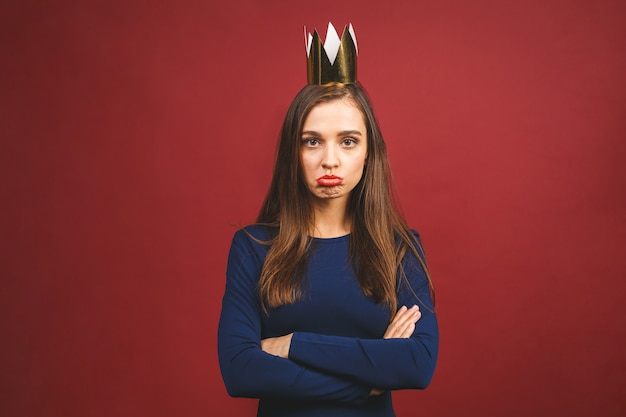 Portrait with copyspace empty place of confident proud arrogant young woman with gold crown on her head isolated on red background.