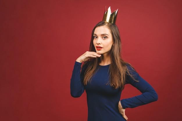 Портрет с copyspace пустое место уверенно гордой высокомерной молодой женщины с золотой короной на голове, изолированных на красном фоне.