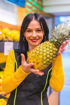 과일 가게에서 일하는 갈색 머리 백인 과일 소녀의 손에 파인애플 초상화