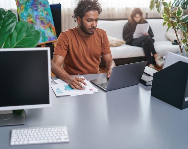 ノートパソコンとシャツのコンセプトを持つ真面目なインドのスタイリストの暖かい雰囲気の肖像画。男性デザイナーと彼の中小企業。