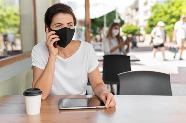 マスクを身に着けているタブレットでテラスで肖像画の女性
