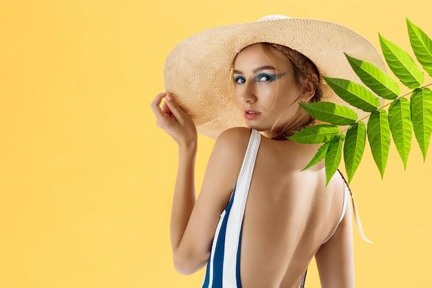 Ritratto di una donna su una spiaggia che indossa un cappello