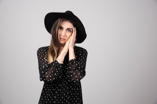 Portrait of woman in black hat holding her face.