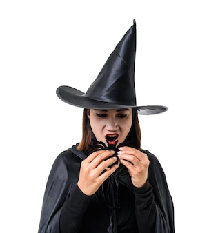 Portrait of woman in black scary witch halloween costume standing with hat