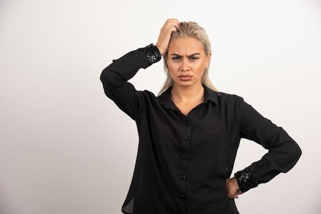Ritratto di donna in camicia nera in posa su sfondo bianco. foto di alta qualità