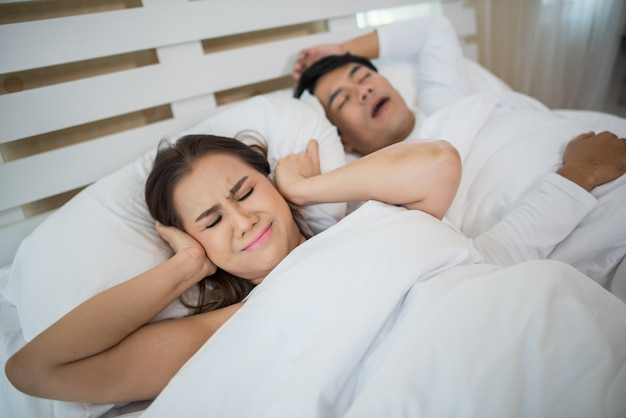 Portrait of woman blocking ears with man sleeping snoring on bed
