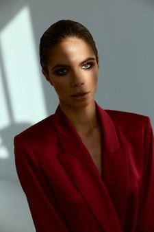 Portrait of a woman bright makeup red jacket studio