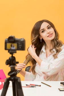 Portrait of woman brushing hair on camera