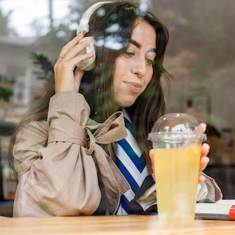 Portrait of woman in cafe with fresh lemonade and headphones
